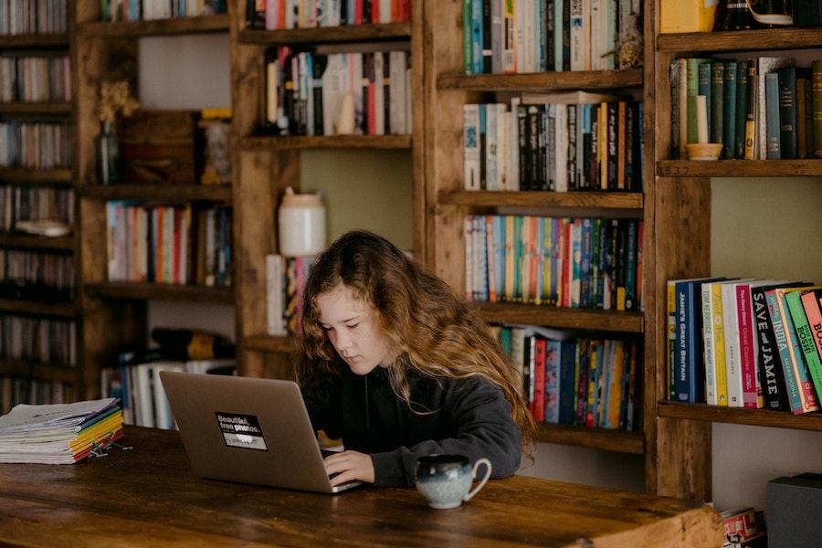 adolescente qui étudie dans une bibliothèque